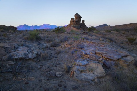 Rock formation at sunrise with Chisos Mountains in the background.