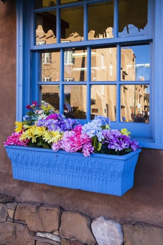 Window and flower box with reflection of Santa Fe building.