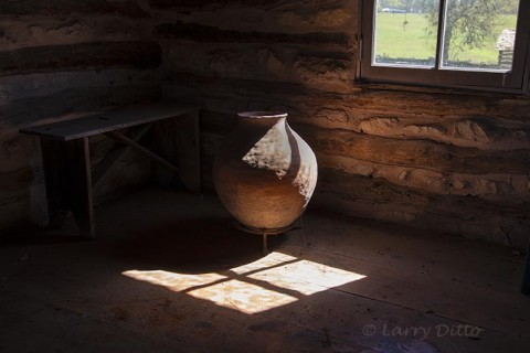 Clay jar by log cabin window.
